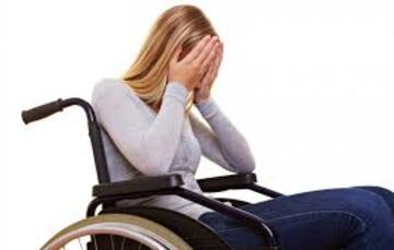 Mujer con discapacidad en silla de ruedas se cubre el rostro con las manos denotando tristeza