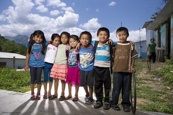 Niñas y niños de Chiapas ante la cámara, junto al campo deportivo de su poblado.