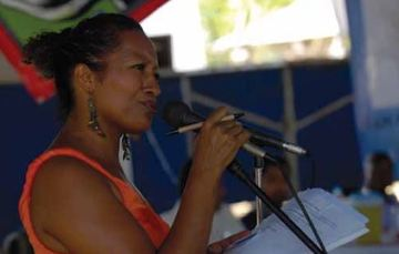 Una mujer afro hablando al micrófono