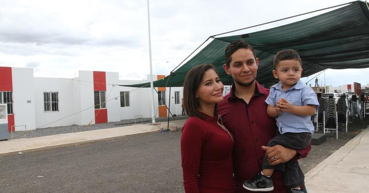 Pareja de padres jóvenes con su hijo frente a su nuevo hogar en Durango.