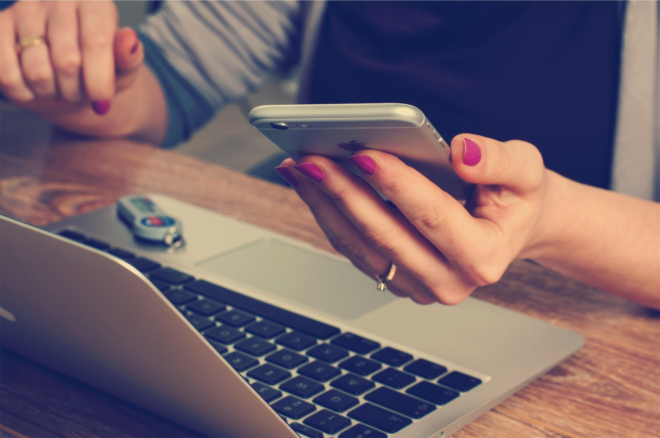 Manos de una persona con un teléfono móvil y un computador