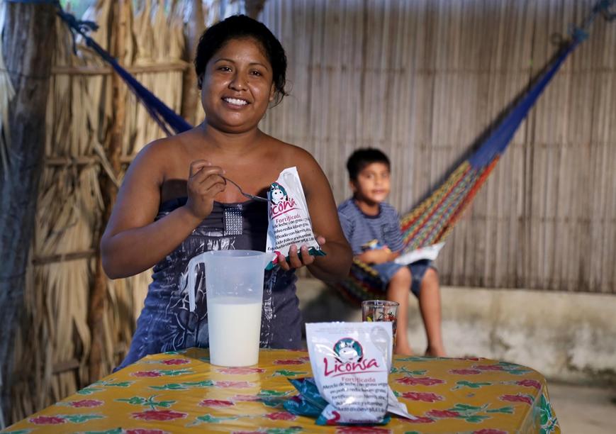 Señora y niño consumiendo leche Liconsa en una casa de madera