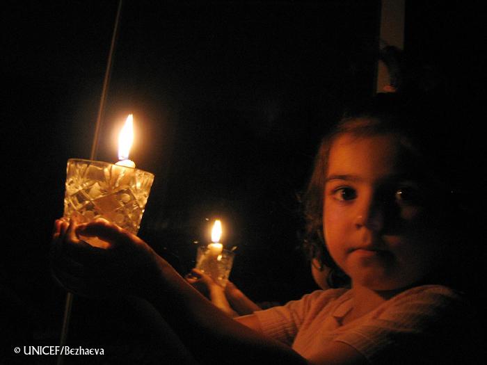 Niña pequeña sostiene vela encendida con una mano.