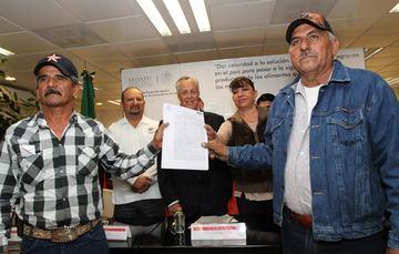 Propietarios de los ejidos levantan sus nuevos títulos de propiedad.