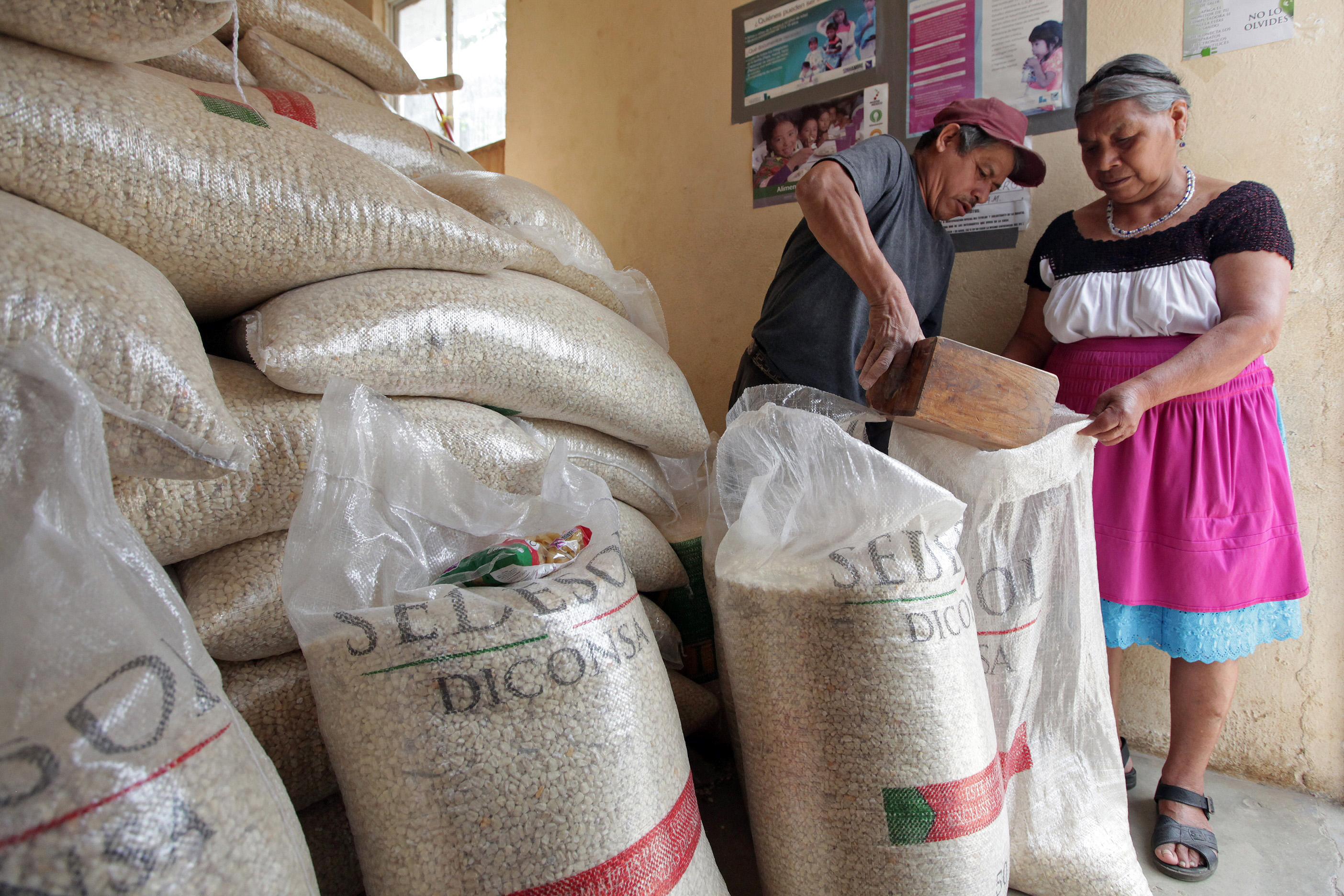 Dos adultos mayores comprando maíz en almacén de Diconsa