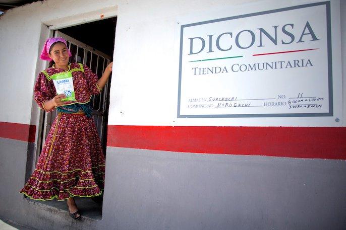 Mujer indígena con una bolsa de leche liconsa