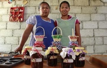 Dos mujeres frente a sus productos de un proyecto productivo de conservas