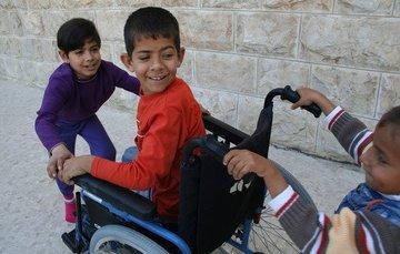 Dos niños ayudando a un niño con discapacidad en silla de ruedas
