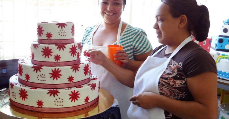 Dos mujeres decorando un pastel.