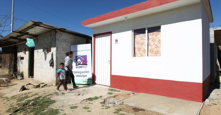 Una madre con su hijo entrando a su nuevo cuarto adicional en la localidad de Acaxochitlán, Hidalgo.