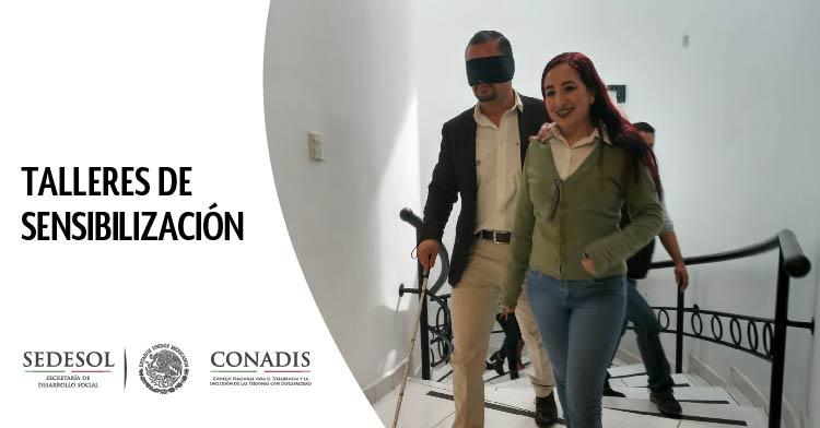 Funcionarios públicos tomando un taller de sensibilización, uno simula tener discapacidad visual con ojos vendados y bastón blanco, es guiado por otra persona.