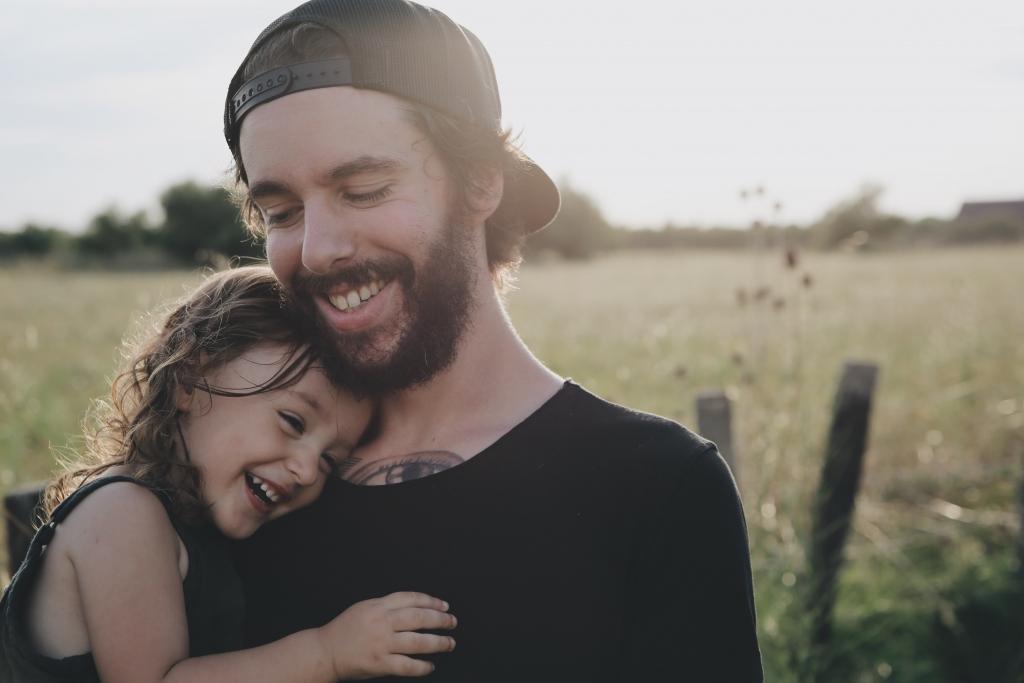 Papá joven sostiene a su hija en brazos y están sorrientes