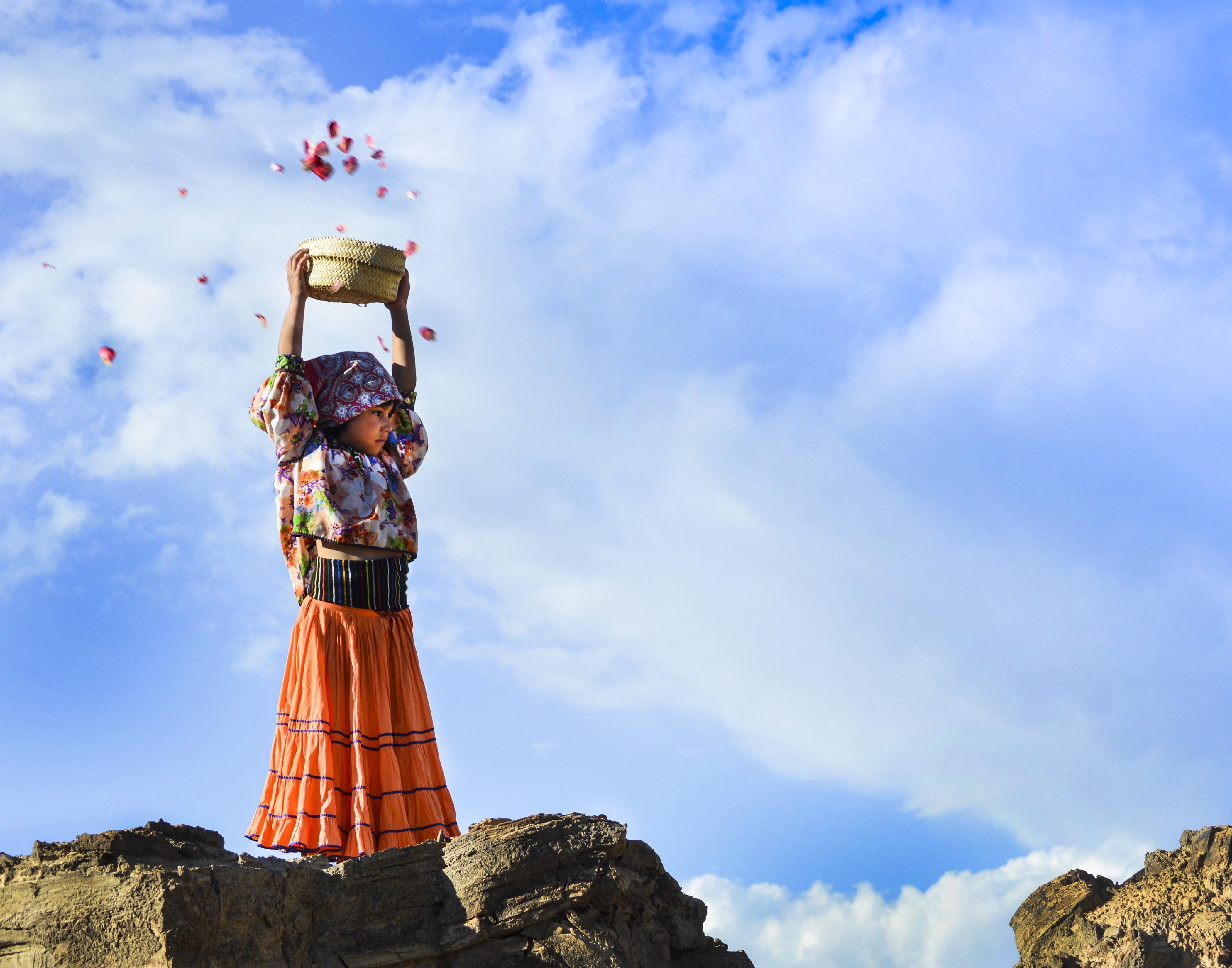 Niña en la cierra de Chihuahua, vestimenta Taraumara, sostiene una canasta con sus brazos en alto, de ella salen pétalos al aire.