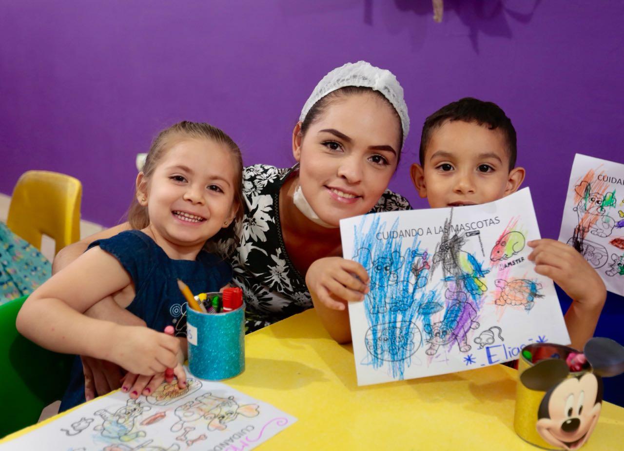 Niño mostrando una tarea junto a educadora y niña en una de las estancias infantiles de Sedesol