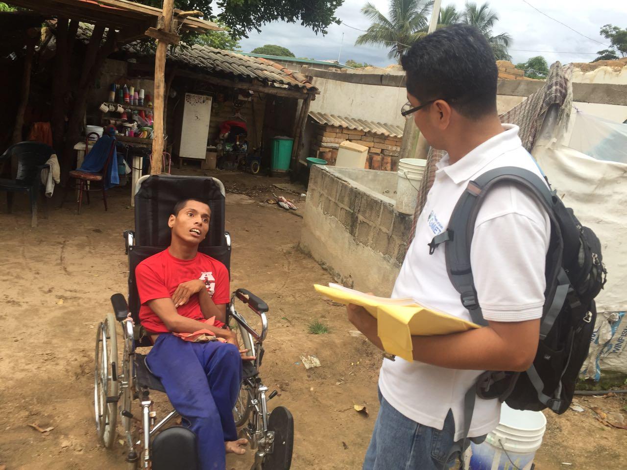 Servidor Público del CONADIS platica con una persona con discapacidad en silla de ruedas
