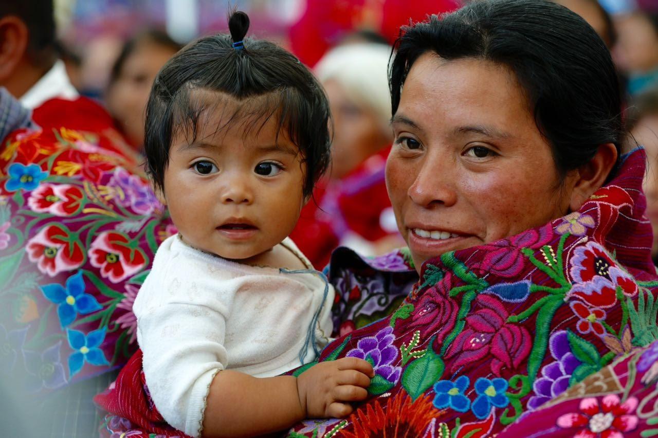Mujer con vestido tradicional mexicano cargando a una bebé