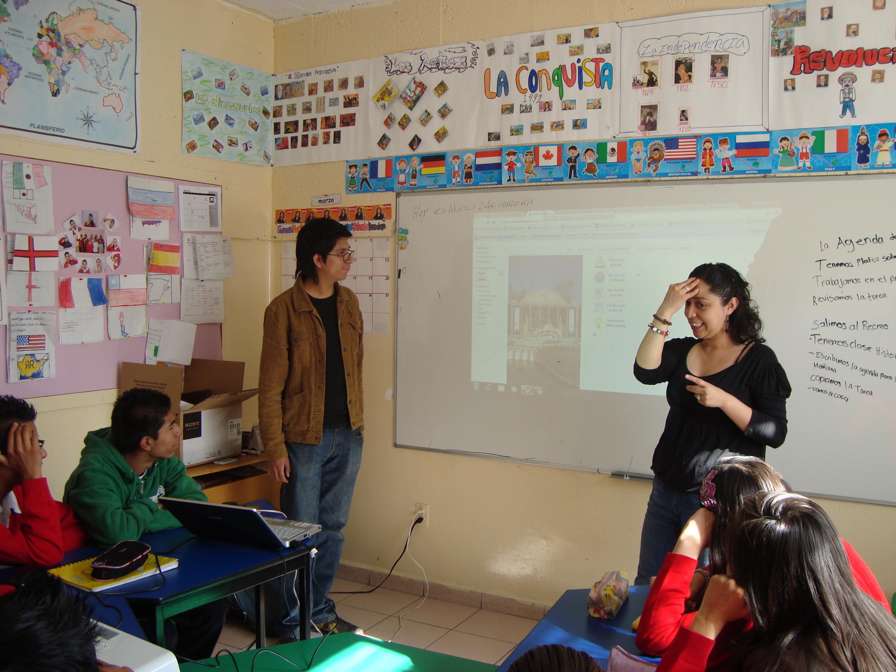 Estudiante expone en Lengua de Señas Mexicana durante la clase, la observan sus compañeros