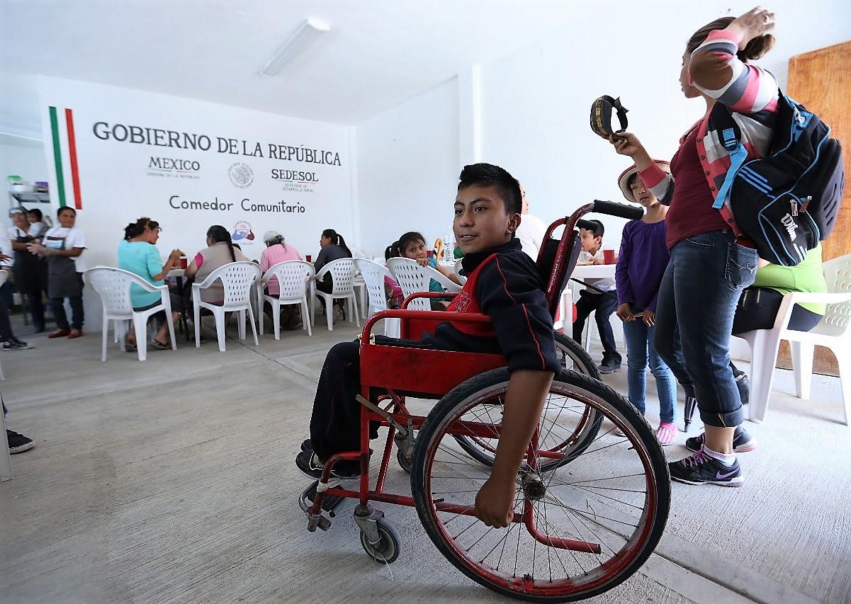 Muchacho joven en silla de ruedas en un Comedor Comunitario