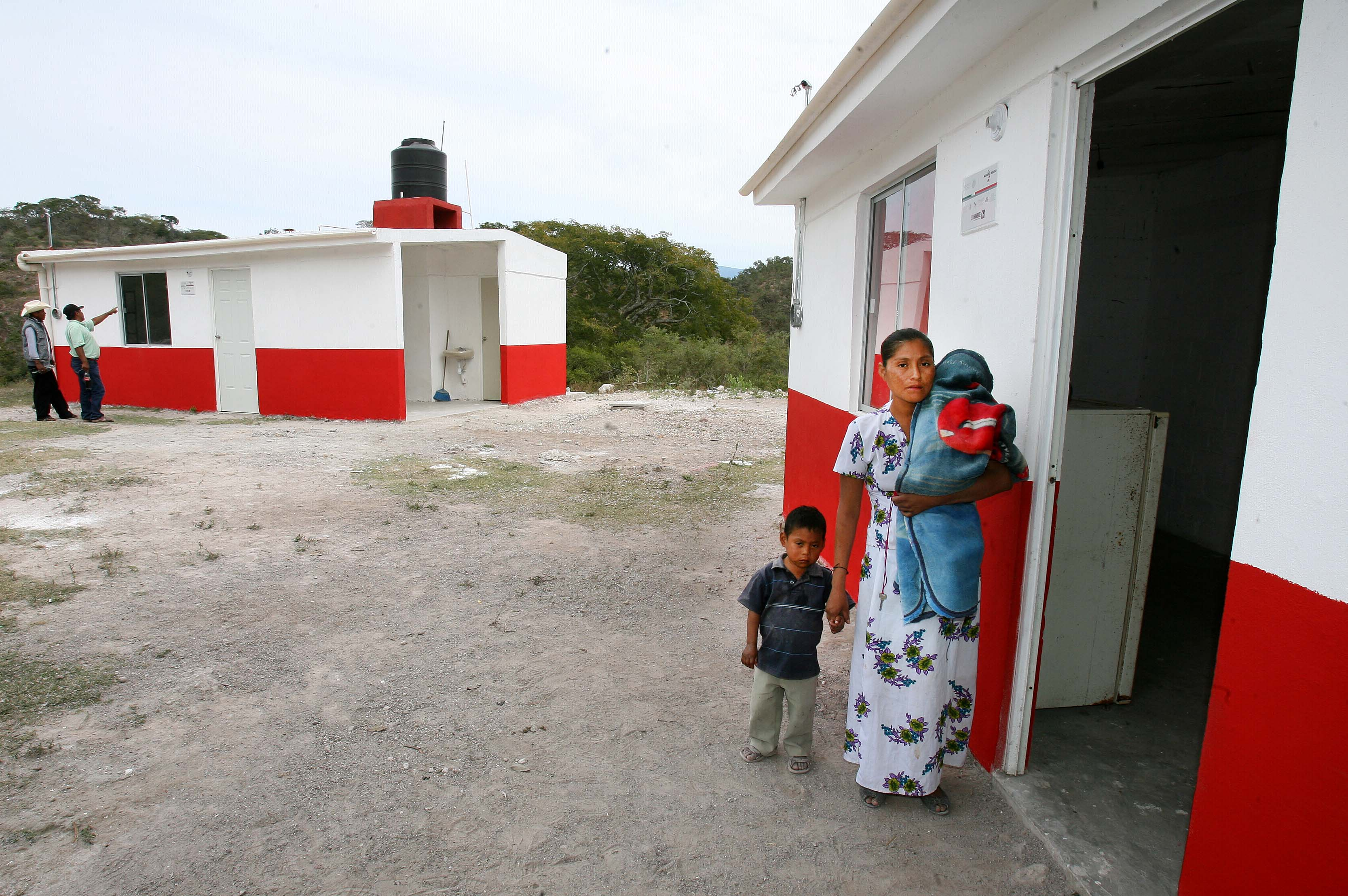 """Mujer con sus dos hijos a la entrada de su """"Cuarto Rosa"""""""