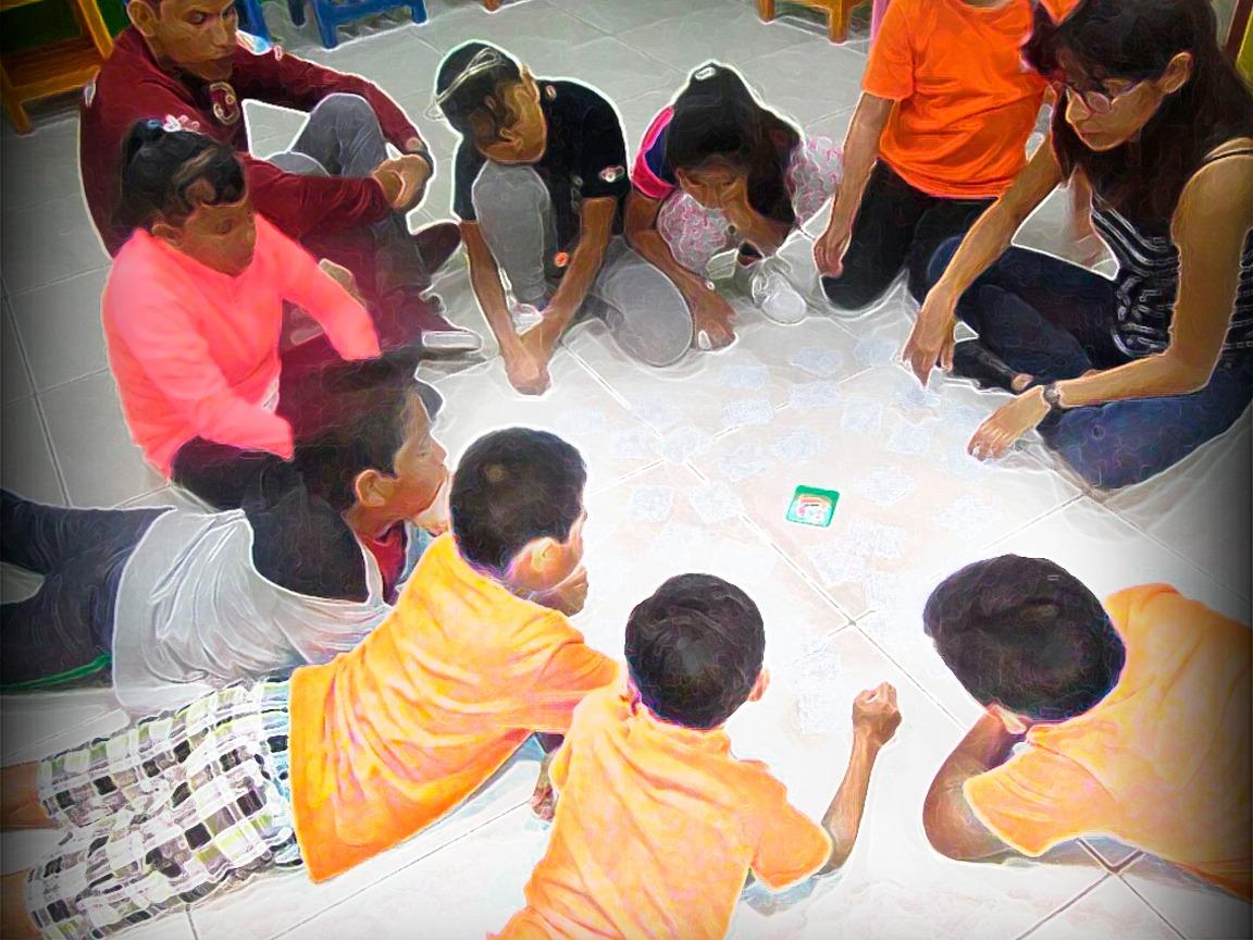 6 niños y tres niñas jugando en el piso un juego de mesa, acompañados de una mujer joven