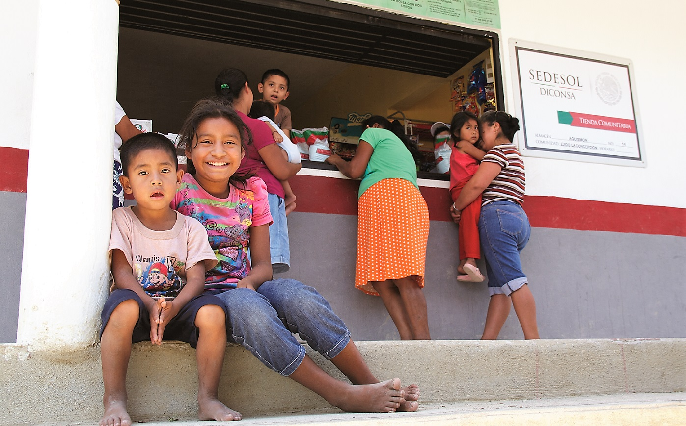 Tienda Comunitaria Diconsa con algunas familias y dos niños en primer plano