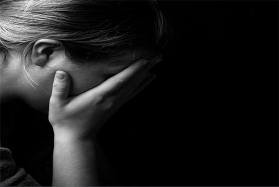 Mujer joven se cubre el rostro con ambas manos en señal de desesperación