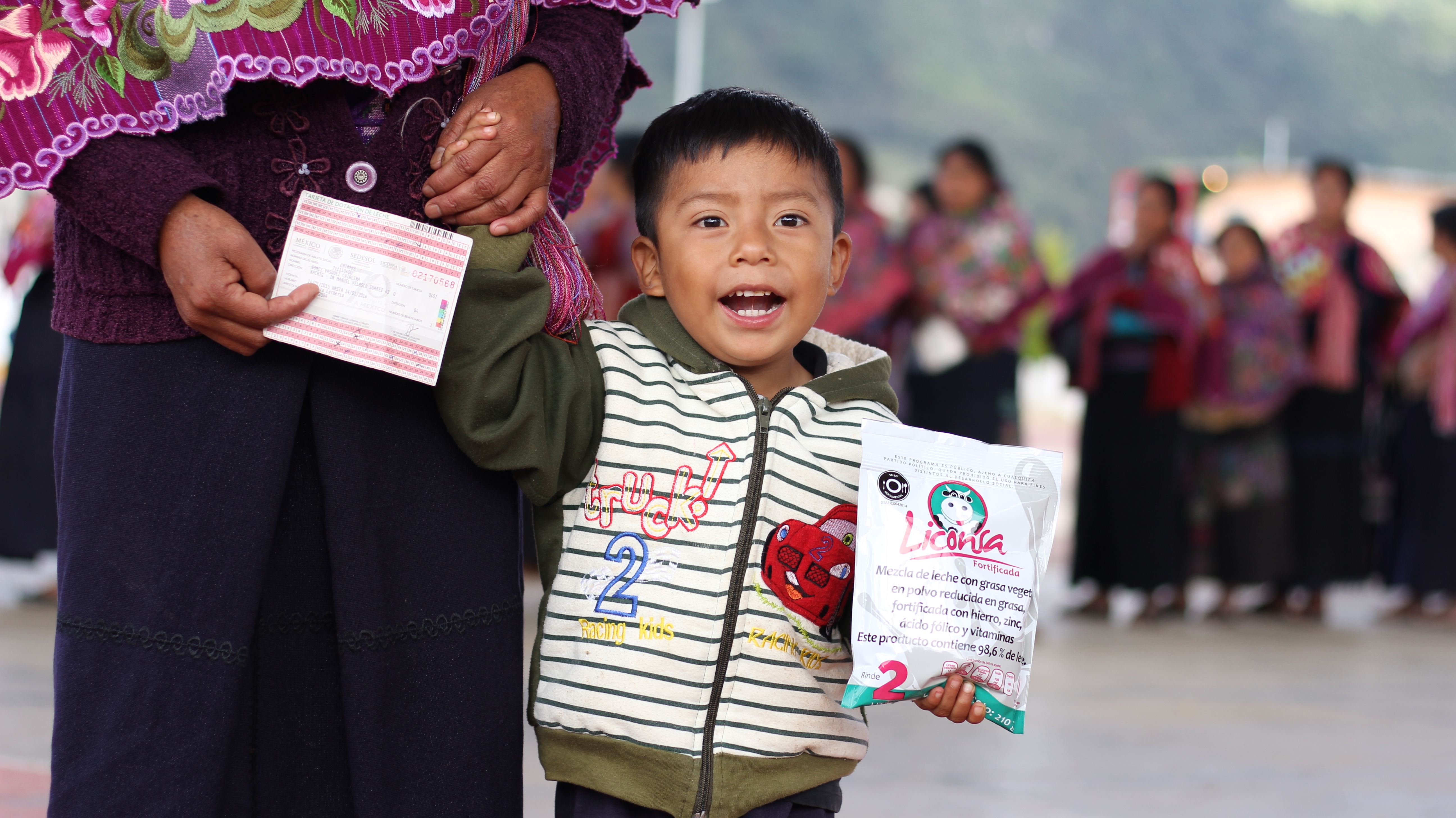 Niño con sobre de leche Liconsa de la mano de su mamá
