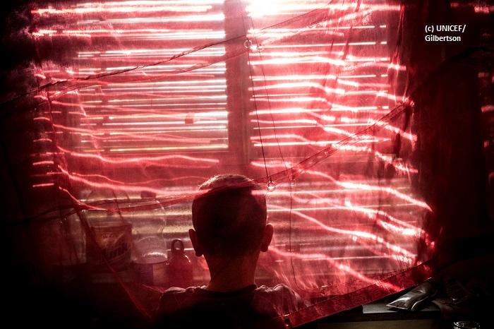 Niño de espaldas, frente a una ventana con persianas, en su momento de intimidad.