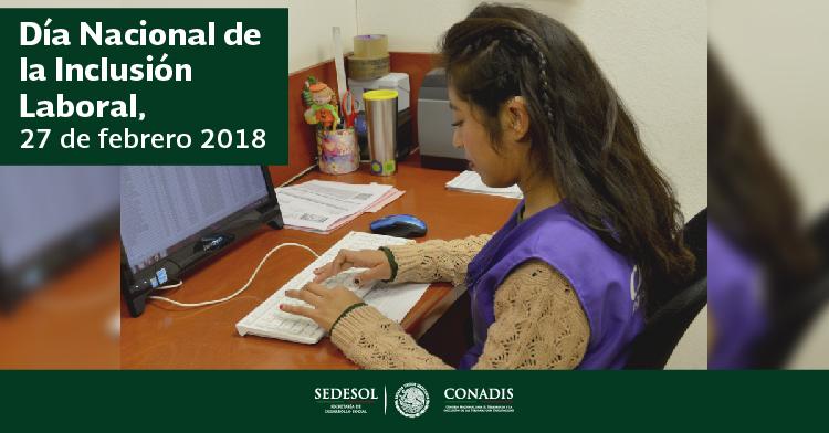 Es una chica con discapacidad auditiva trabajando en una computadora, que se encuentra sobre un escritorio.