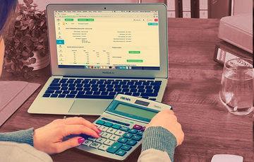 Ilustración de una mujer que esta manipulando una computadora tipo laptop y una calculadora científica