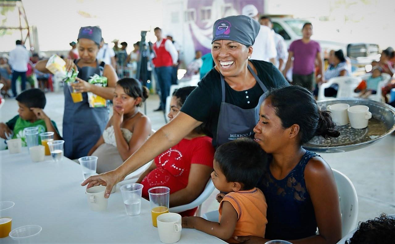Mujer voluntaria dando alimentos a otras mujeres en un comedor comunitario