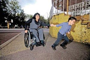 Es un parque al lado de un kiosko, una mujer en silla de ruedas que es jalada de la mano por su hijo, un menor de aproximadamente 5 años de edad.