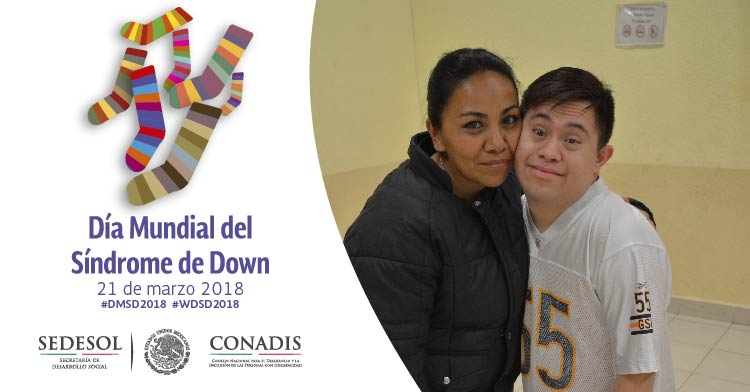 Es un joven con Síndrome de Down con su mamá abrazándolo y uniendo su mejillas.