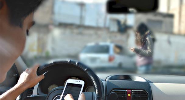 Un hombre manejando y usando celular