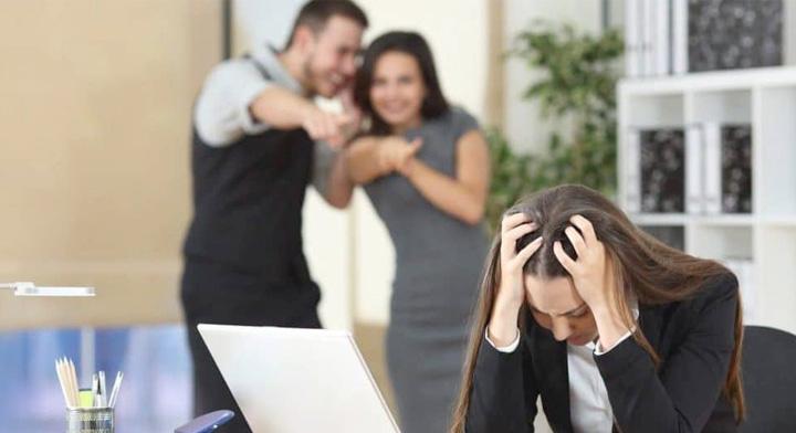 Mujer recibiendo acoso laboral por un hombre y mujer.