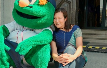Fotografía de Georgina Jesús, Directora de Marketing de la Liga Mayor de Béisbol en México junto a una botarga.