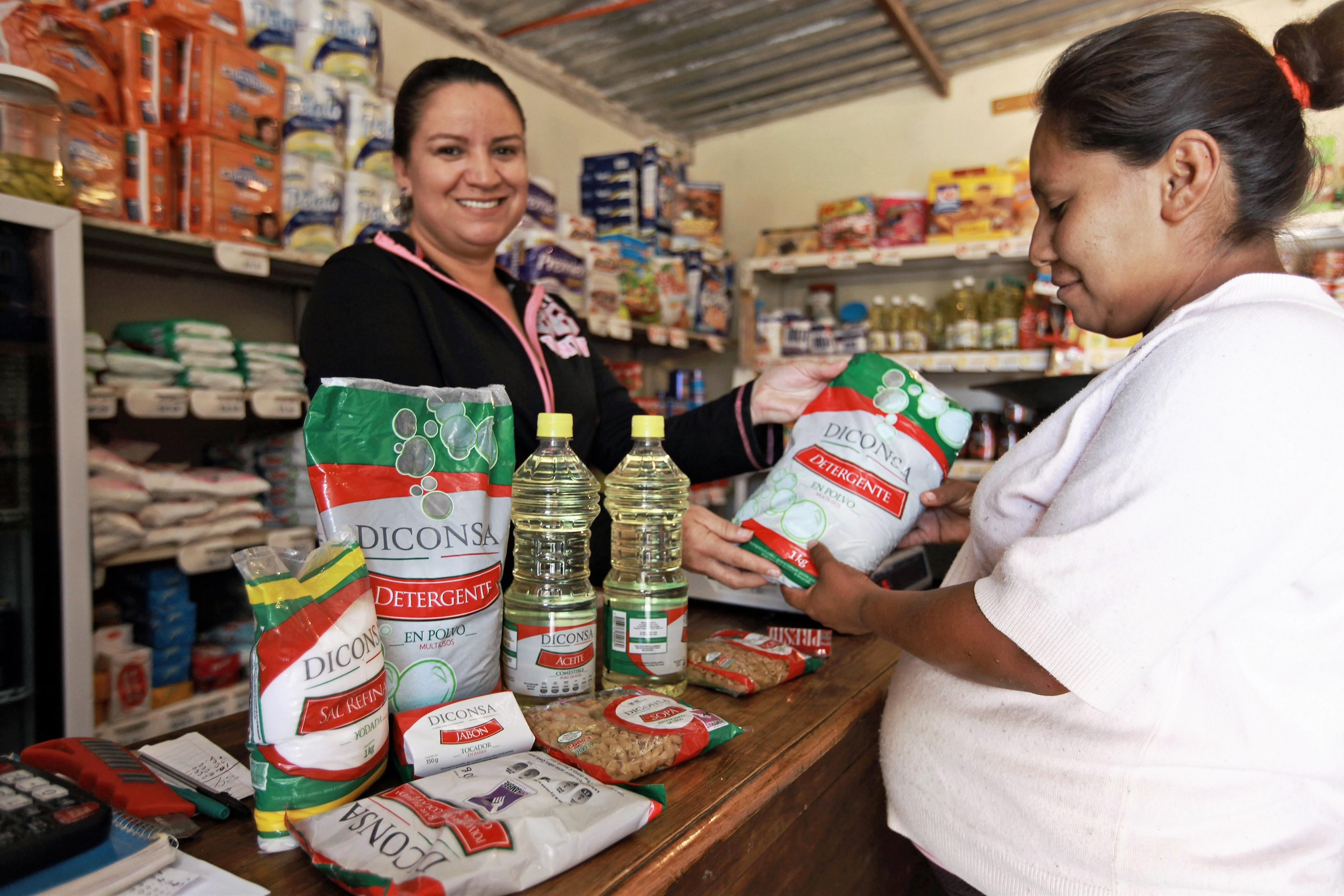 Mujer embarazada viendo productos Diconsa en una tienda junto a la vendedora