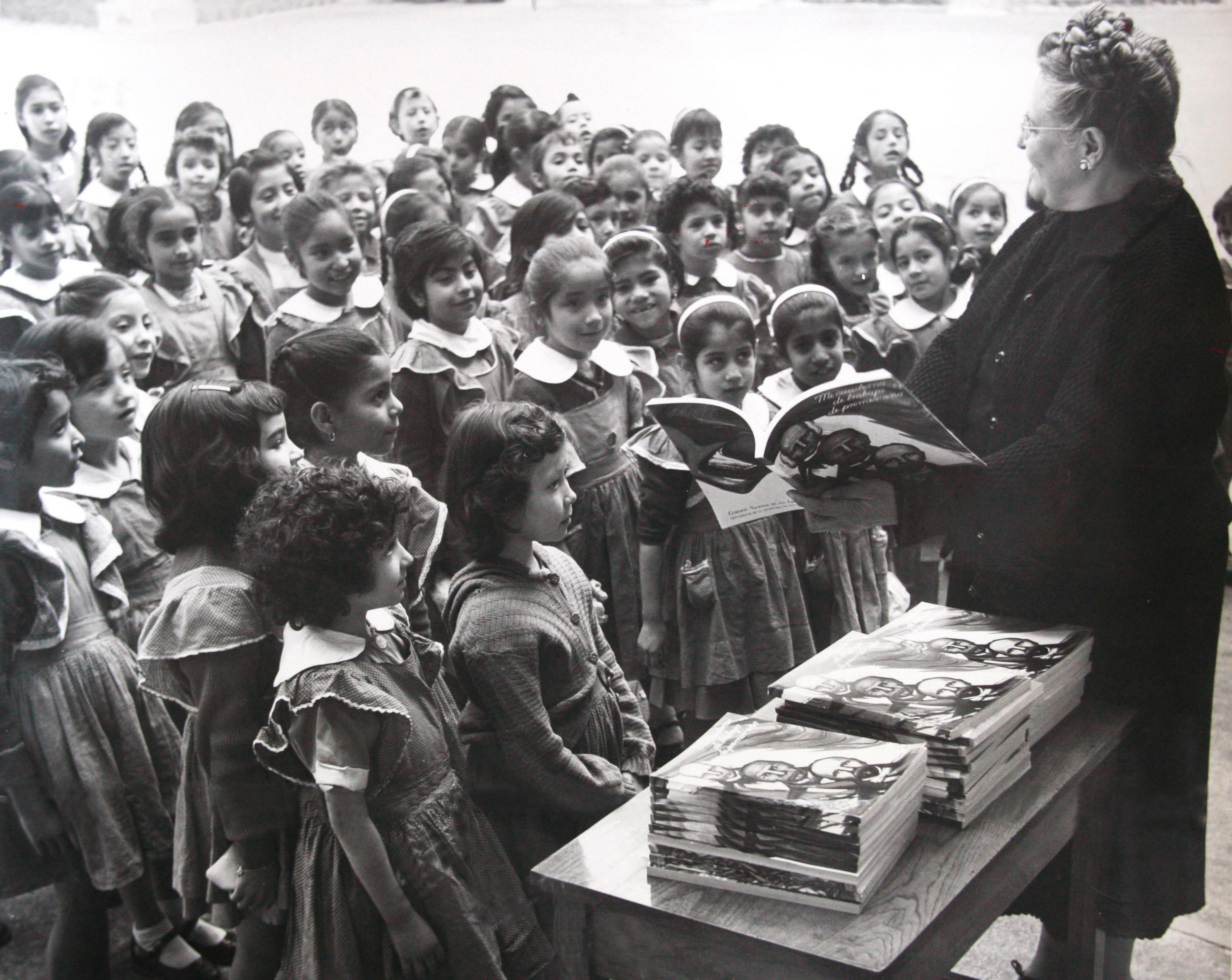 Maestra reparte los primeros libros de texto gratuitos.