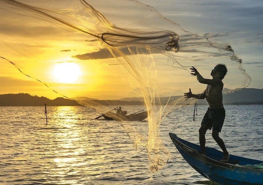 Vista general de pescador lanzando red de pesca al océano durante el atardecer.
