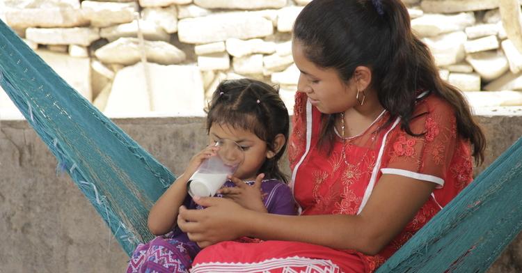 Mamá dando un vaso de leche a su hija