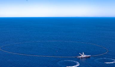 Aérea de embarcación extendiendo perímetro de  red para retirar sargazo