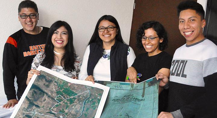 Compañeras y compañeros del Departamento de Cartografía y Proceso Foto Mecánico con plano del Archivo General Agrario (AGA) e imagen satelital.