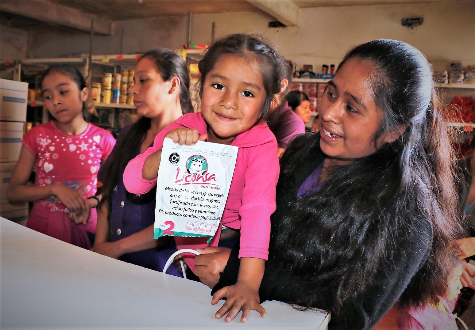 Mujer cargando a una niña sonriendo que trae un sobre de leche Liconsa en la mano