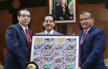 Autoridades de Pronósticos y Lotería Nacional sosteniendo el cuadro conmemorativo al billete electrónico del 40 aniversario de Pronósticos.