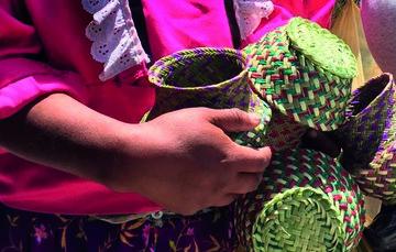 Artesana sosteniendo artesanías de fibra vegetal