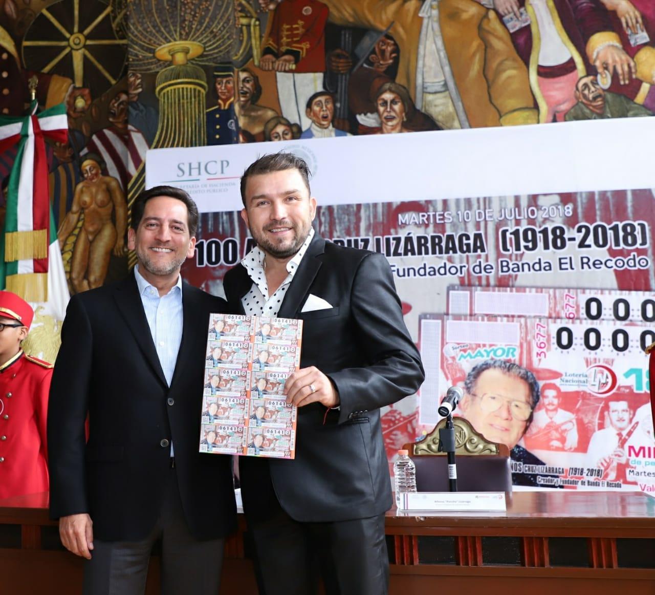 """Fotografía de portada del Lic. Eugenio Garza Riva Palacio, Director General de la Lotería Nacional, quien posa junto a """"Poncho"""" Lizárraga, hijo de Don Cruz Lizárraga. Juntos posan el billete de Lotería."""