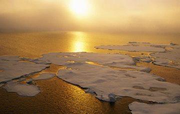Aérea de atardecer del océano donde se muestra el derretimiento de las capas de hielo.