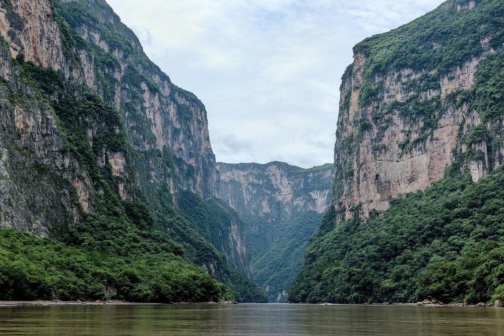 Fotografía con el paisaje del Cañón del Sumidero en Chiapas. Donde se aprecia el cauce del río Grijalva entre las paredes de roca y vegetación del acantilado.