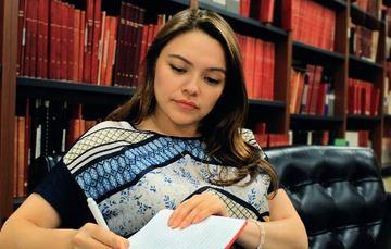 Jovén de sexo femenuno escribiendo en su libreta en una biblioteca.