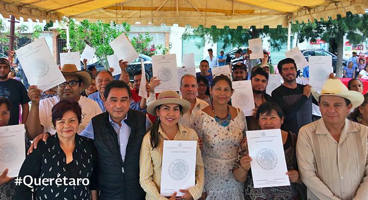Foto grupal con ejidatarios con documento agrario en mano en el estado de Querétaro.